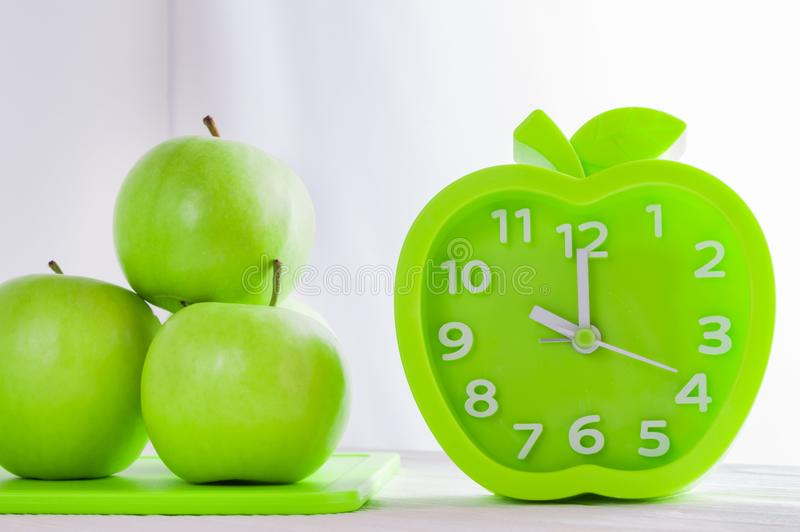 Alarm clock and green apples on white wooden table. Good morning, healthy morning or diet concept. Green alarm clock in the shape of an apple and fresh green royalty free stock images