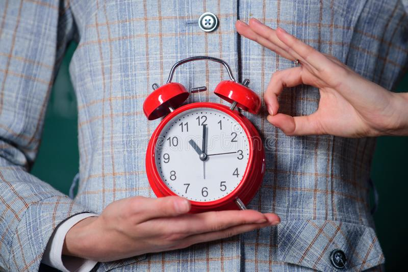 Alarm clock in hands of teacher or educator classroom background. School discipline concept. Schedule and regime. Right. On time ok gesture. Alarm clock in royalty free stock images