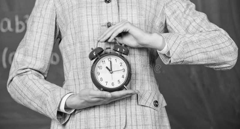 Alarm clock in hands of teacher or educator classroom chalkboard background. School discipline concept. Schedule and. Regime. Alarm clock in female hands close stock photography