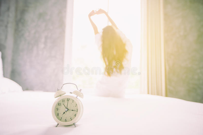 Alarm clock having a good day of Asian woman waking up in her be. D fully rested and open the curtains in the morning to get fresh air stock photography