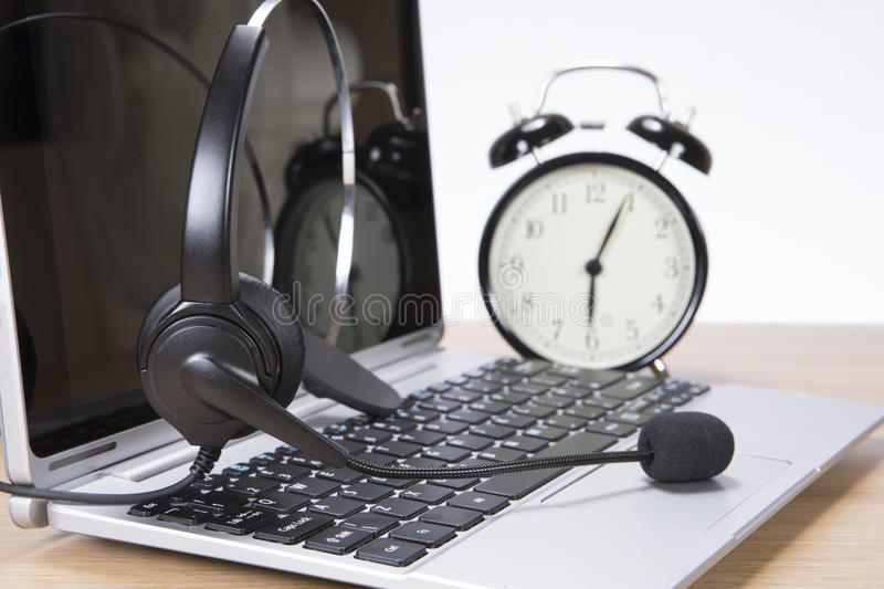 Alarm clock and headset on a laptop computer royalty free stock images