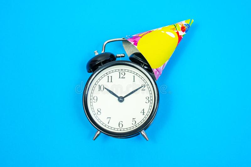 Alarm clock with holiday cap on blue background . Place for text. Top view stock images