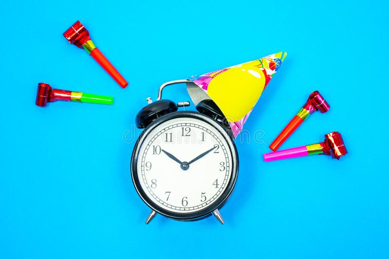 Alarm clock with holiday cap, party blower on blue background. Flat lay. Top view stock photography