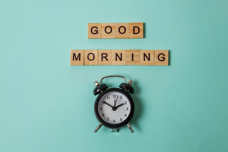 Alarm clock and Inscription GOOD MORNING letters word on blue background. Simply flat lay design alarm clock and Inscription GOOD MORNING letters word on blue stock image