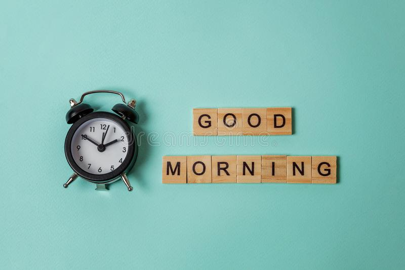 Alarm clock and Inscription GOOD MORNING letters word on blue background. Simply flat lay design alarm clock and Inscription GOOD MORNING letters word on blue royalty free stock photos