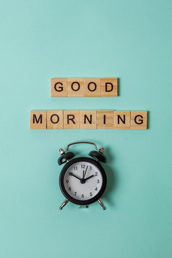Alarm clock and Inscription GOOD MORNING letters word on blue background. Simply flat lay design alarm clock and Inscription GOOD MORNING letters word on blue stock photo
