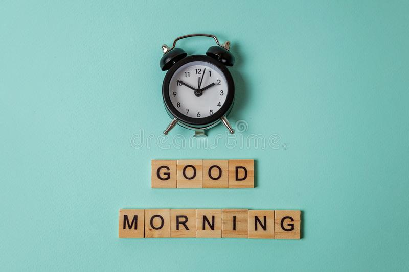 Alarm clock and Inscription GOOD MORNING letters word on blue background. Simply flat lay design alarm clock and Inscription GOOD MORNING letters word on blue royalty free stock photography