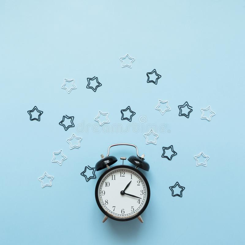 Alarm clock isolated on blue background. Wake-up time. Back to school flat lay royalty free stock photo