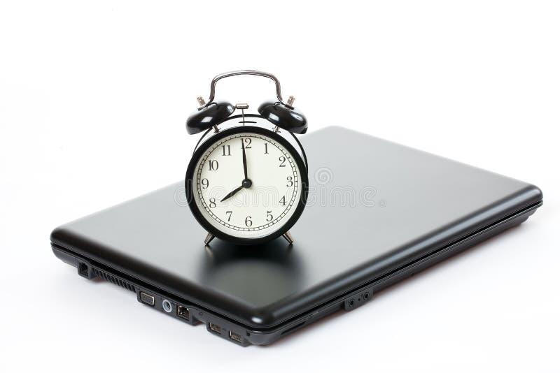 Alarm clock and laptop stock photography