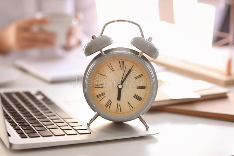 Alarm clock with laptop on light table in office stock image