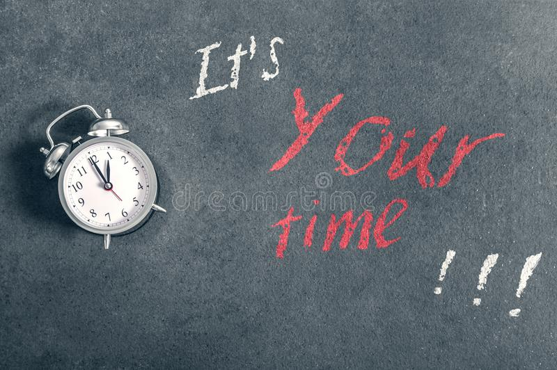 Alarm clock lies on a countertop with a motivational inscription. `It`s Your time stock photo