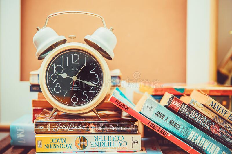 The alarm clock on a lots of books, Many people spend time to reading novel during self quarantine stay home that is good for royalty free stock photos