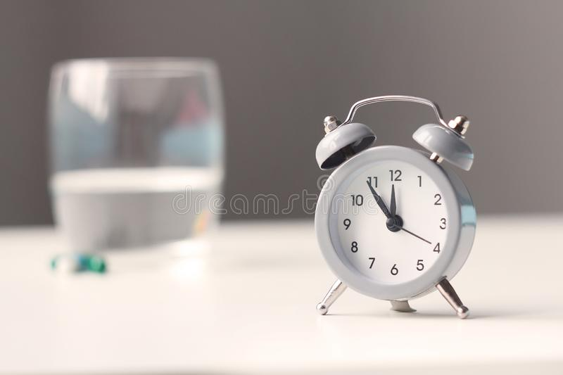 Alarm clock and medical pills on bedside table.Healthcare and medicine royalty free stock images