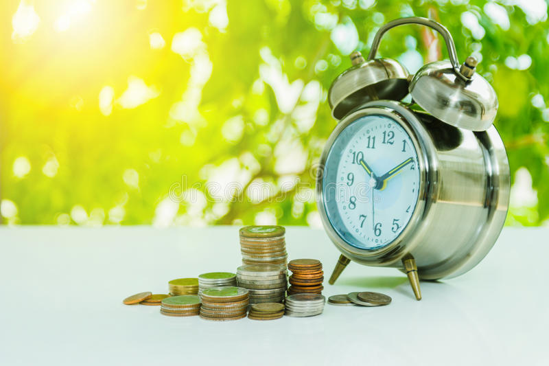 Alarm clock and money,coins stack and alarm clock on background,finance concept,business background and selective focus. royalty free stock photography