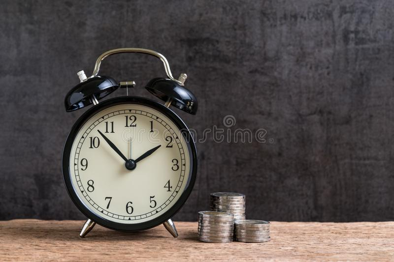 Alarm clock with money stack of coins on wooden table and black royalty free stock photos
