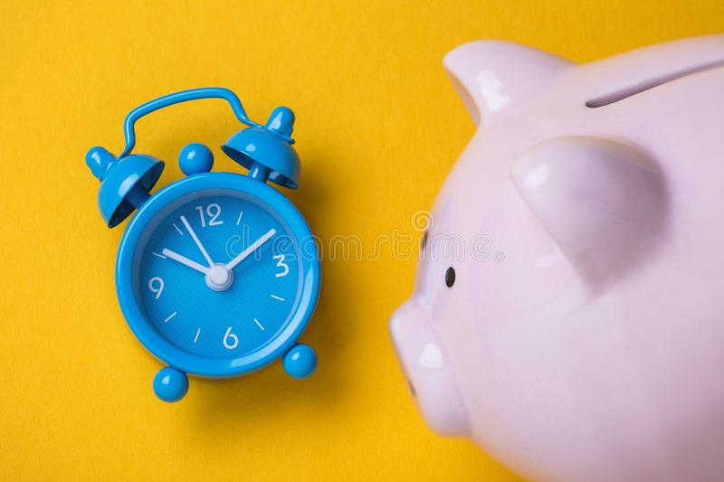 Alarm clock and moneybox on the table. Time to save money. Alarm clock and moneybox on the table, top view. Time to save money royalty free stock photography