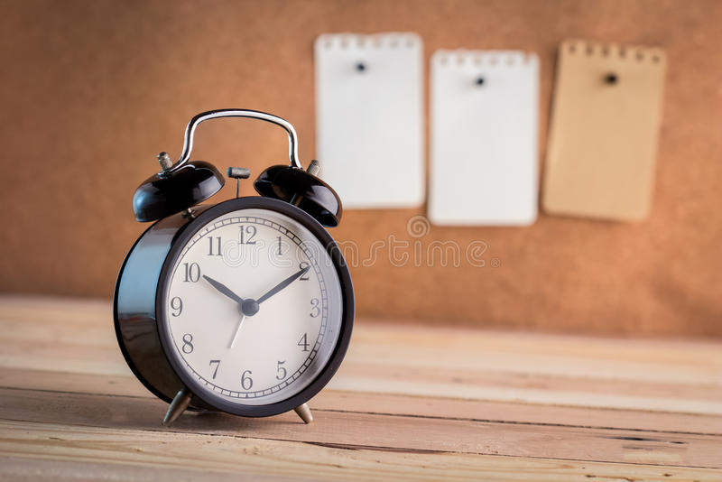 Alarm clock with note paper pin on cork board background stock photo