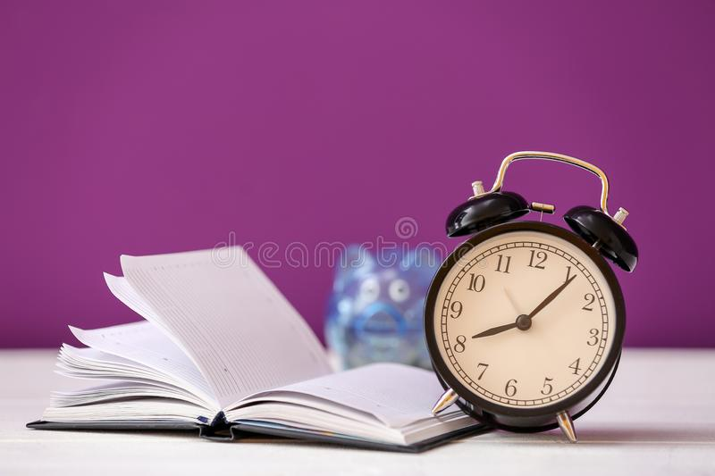 Alarm clock with notebook on light table royalty free stock image