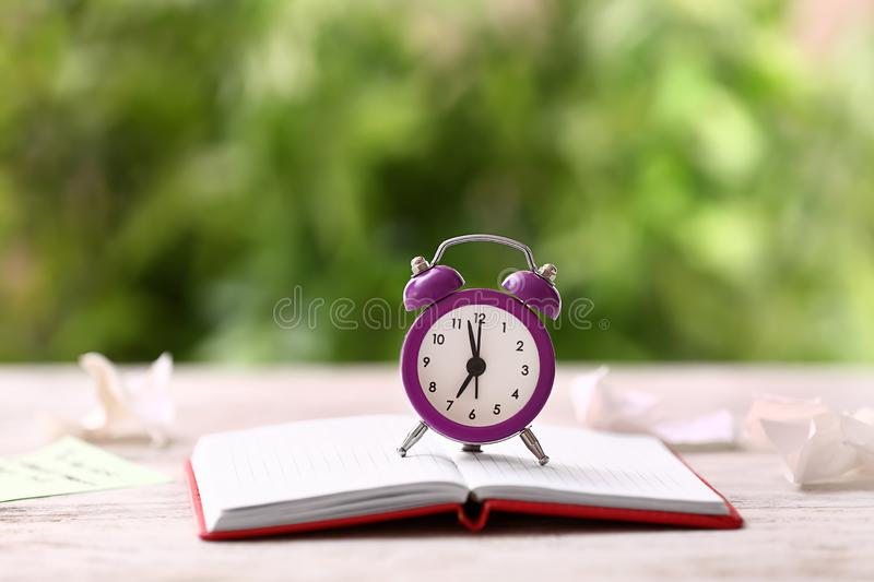 Alarm clock with notebook on wooden table outdoors stock photo