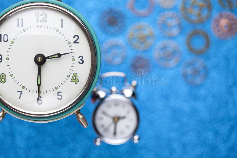 Alarm clock and parts of watch on blue background. Alarm clock and parts of watch on blue abstract background royalty free stock photo