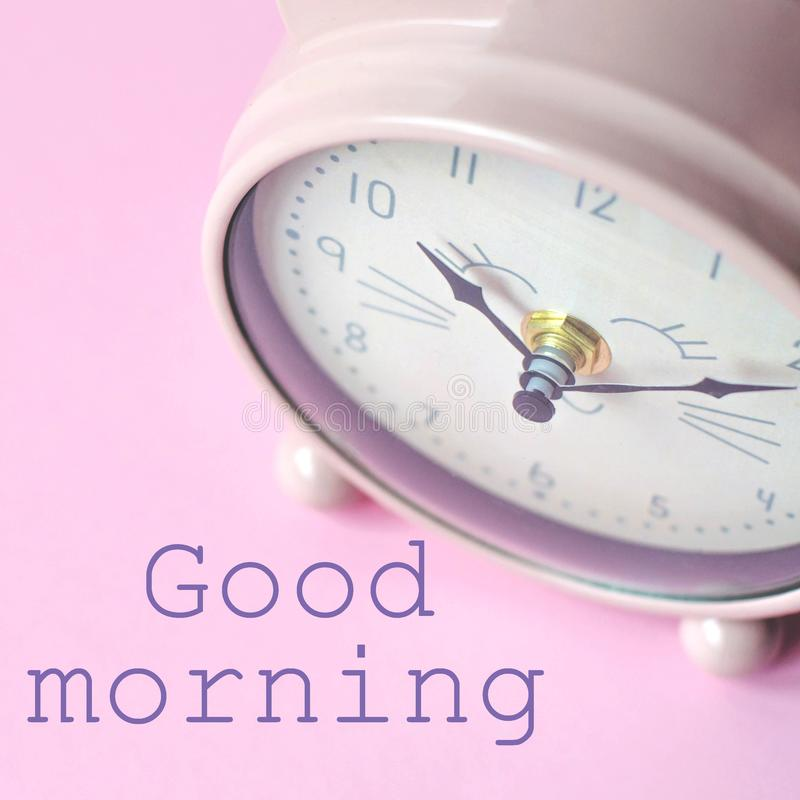 The alarm clock on a pink background and the text good morning. Square photo with an alarm clock in the shape of a cat on a pink background and the text good royalty free stock photo
