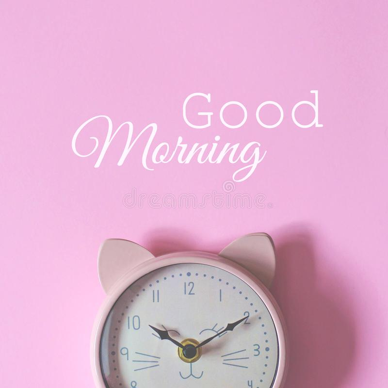 The alarm clock on a pink background and the text good morning royalty free stock image