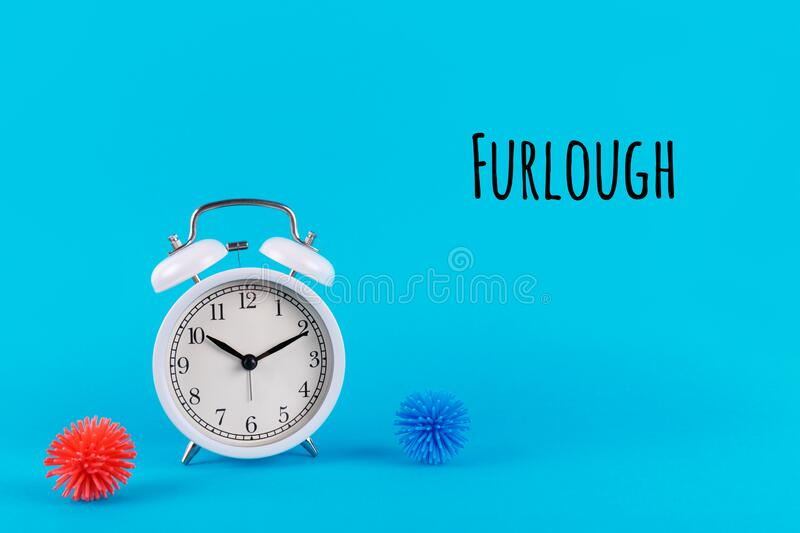 Alarm clock and plastic balls as viruses on the blue background with Furlough wording. Epidemic, social isolation. Coronavirus COVID-19 concept. Option with royalty free stock image