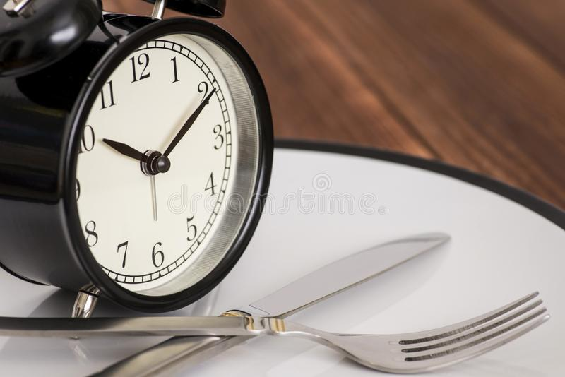 Alarm clock on plate with knife and fork on wooden background. Time to eat. Weight loss or diet concept royalty free stock photos