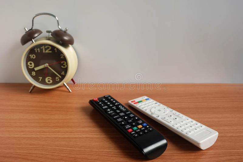 Alarm clock and Remote control TV on wooden floor and White background with copy space stock photos