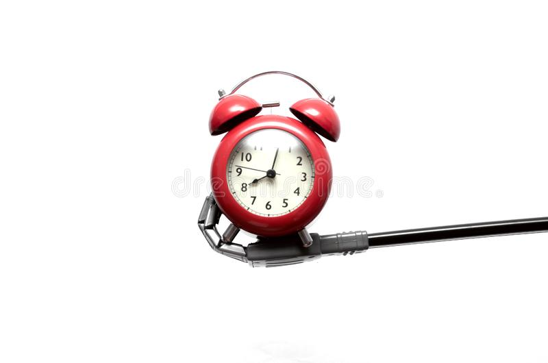 Alarm clock in the robot hand. Toy robot hand is holding a red alkarm clock isolated on white background. Digital reminder royalty free stock image