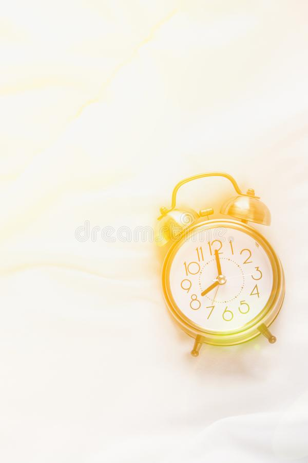 Alarm Clock Showing Eight O`Clock Lying on White Bed Blanket in Bedroom. Bright Golden Morning Sunlight Streaming Through Window. New Day Beginning Waking Up royalty free stock images