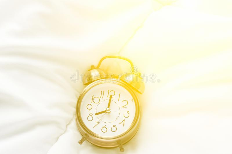Alarm clock showing eight o`clock a.m. lying on white bed blanket in bedroom in bright golden morning sunlight streaming. Through window. New day waking up stock photo