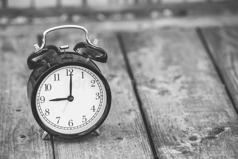 Alarm clock showing five o`clock on wooden background, black and white image. stock photos