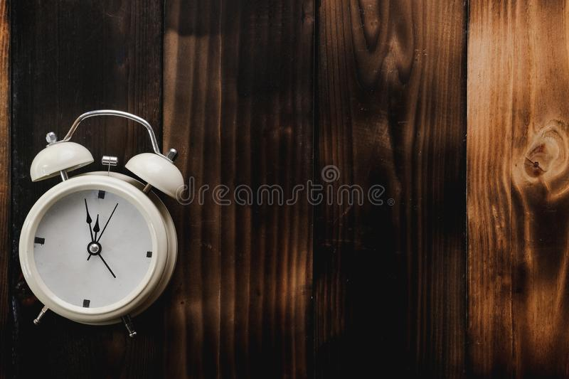 Alarm clock showing almost 12 o clock, on old wooden floor background stock photo