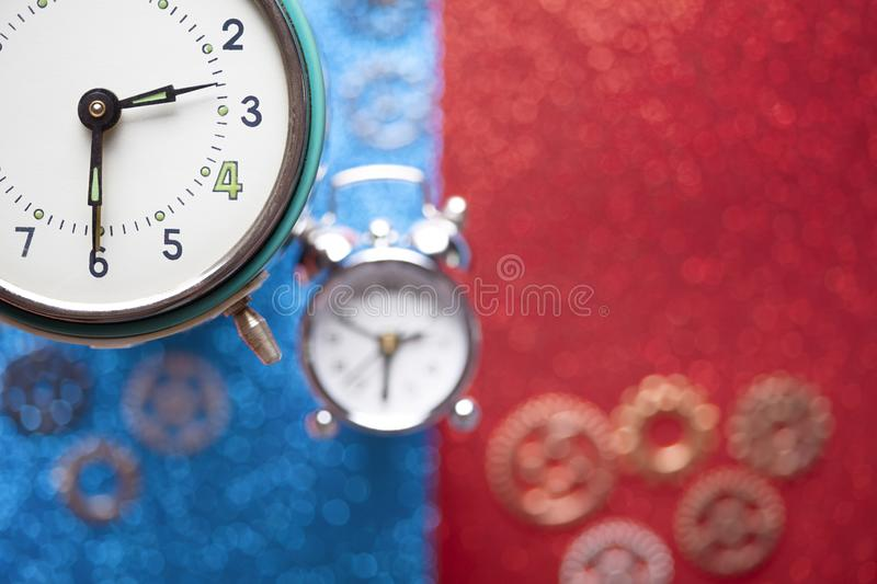 Alarm clock and small parts of watch on red and blue abstract background. Alarm clock and small parts of watch on red and blue abstract table background royalty free stock photography