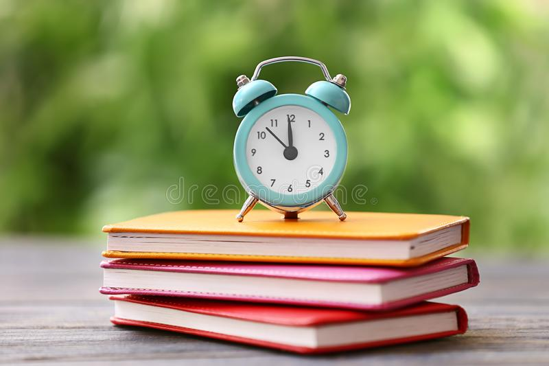 Alarm clock with stack of books on wooden table outdoors royalty free stock images