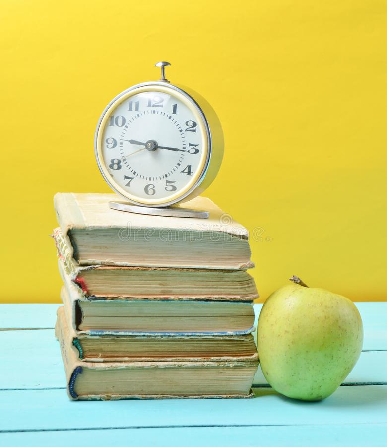 Alarm clock on stack of old books, apple on a yellow background. School concept, education. Alarm clock on stack of old books, apple on a yellow background royalty free stock image