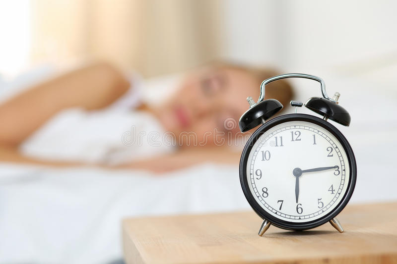 Alarm clock standing on bedside table going to ring early morning royalty free stock photography