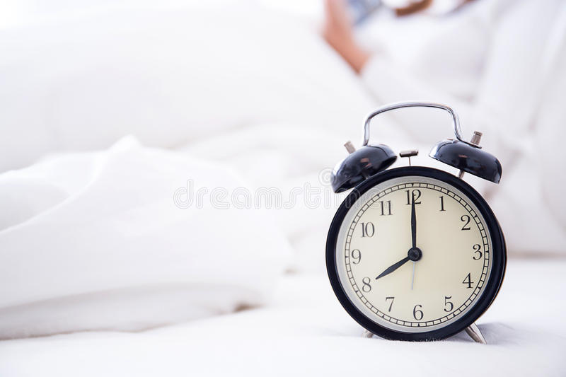 alarm clock standing on bedside table going to ring early morning stock photo