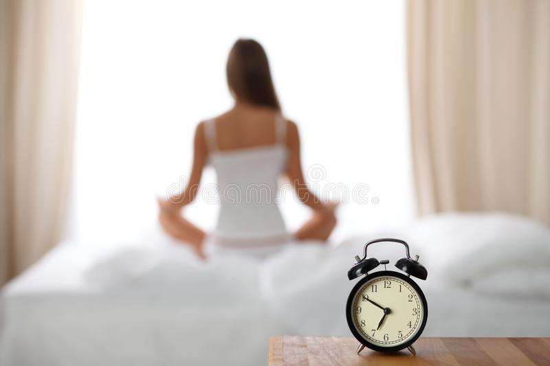 Alarm clock standing on bedside table has already rung early morning to wake up woman in bed sitting in background royalty free stock image