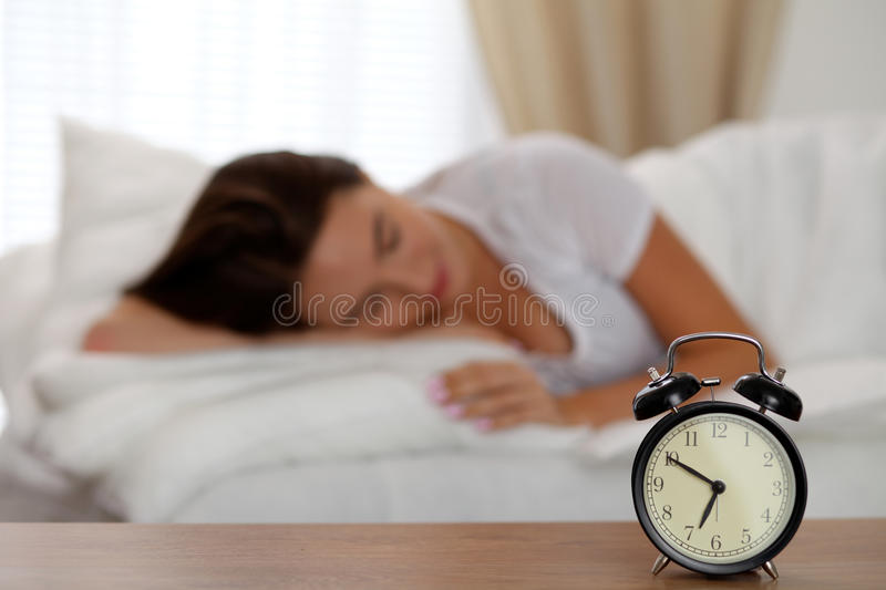 Alarm clock standing on bedside table has already rung early morning to wake up woman in bed sleeping in background. Early awakening, not getting enough sleep stock images