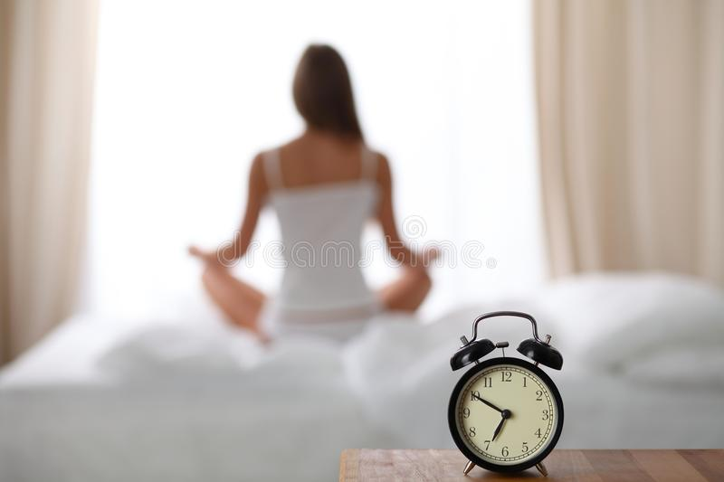 Alarm clock standing on bedside table has already rung early morning to wake up. Woman do yoga in bed in background. Early awakening, healthy lifestyle stock photos