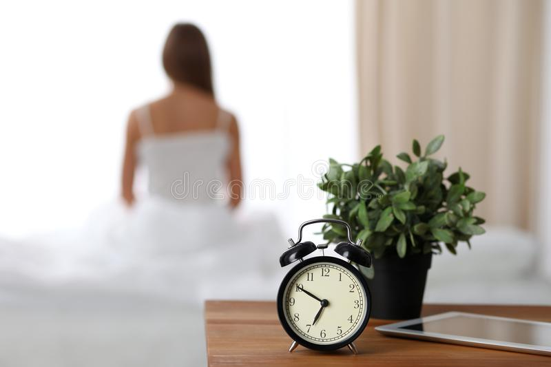 Alarm clock standing on bedside table has already rung early morning to wake up woman is stretching in bed in background stock images