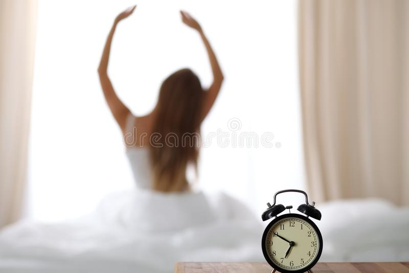 Alarm clock standing on bedside table has already rung early morning to wake up woman is stretching in bed in background stock photo