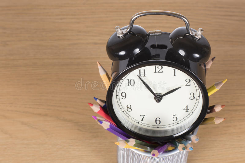 Alarm clock standing on container with pencils royalty free stock photography
