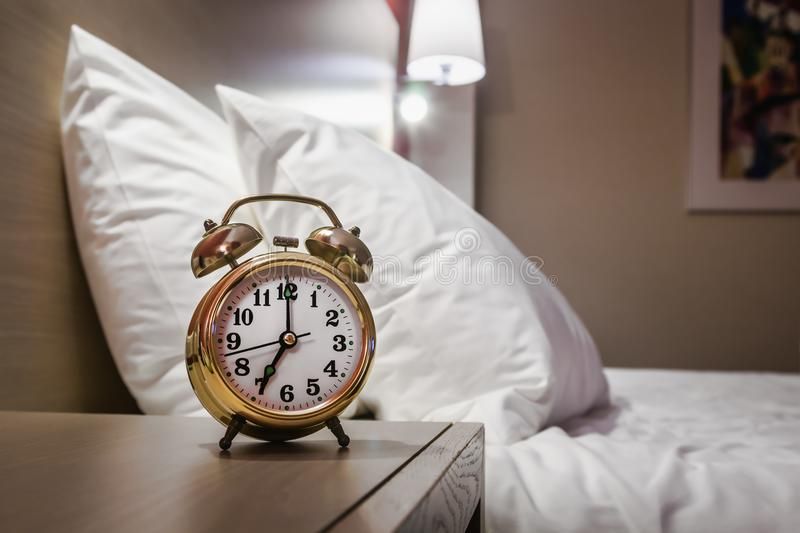 Alarm clock stands on a bedside table. In the room or hotel room stock photography