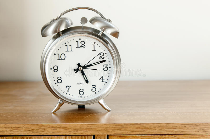 Alarm clock. Stands on the top of a piece of furniture royalty free stock photography
