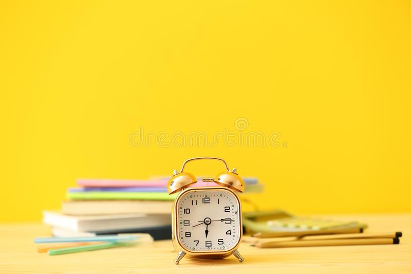 Alarm clock with stationery on wooden table against color background stock photos