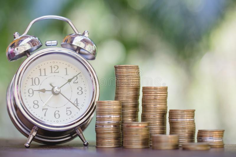 Alarm clock and step of coins stacks on table, time for savings money concept, banking and business, vintage tone stock photography