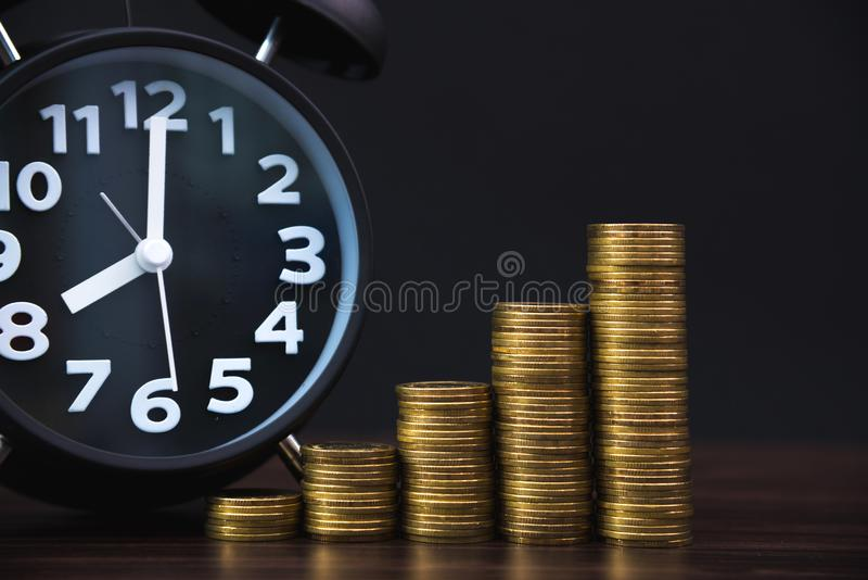 Alarm clock and step of coins stacks on working table in dark room, time for savings money concept, banking and business concept. stock image